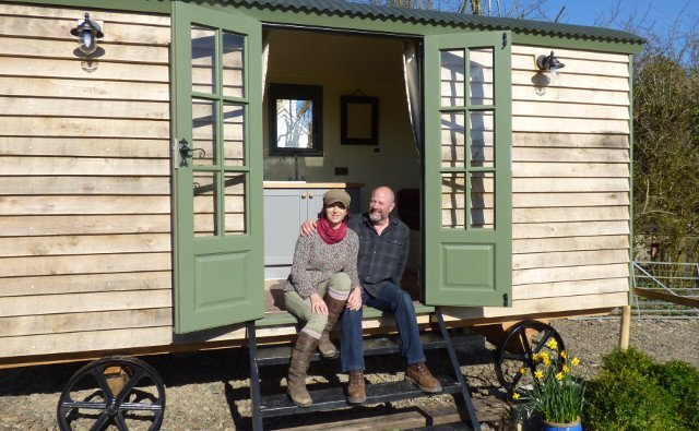Dave and Miri on steps of their glamping shepherd hut