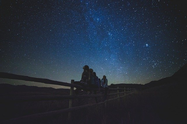 Star-gazers looking at starry night sky